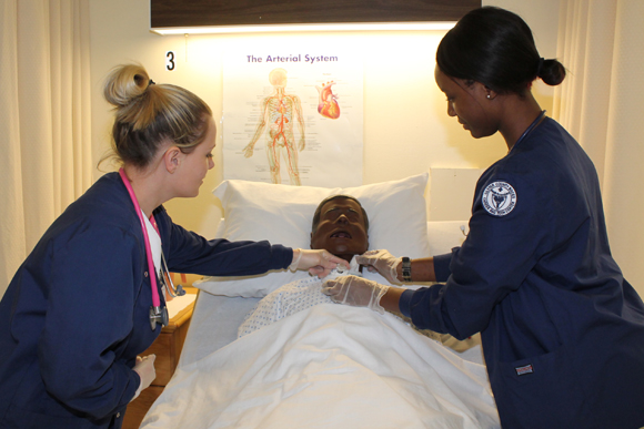 Nursing Assistant students tend to a bedridden mannequin