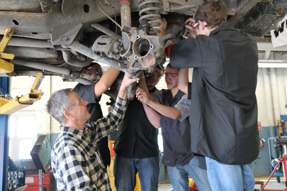 Students observe the underside of an automobile with their instructor