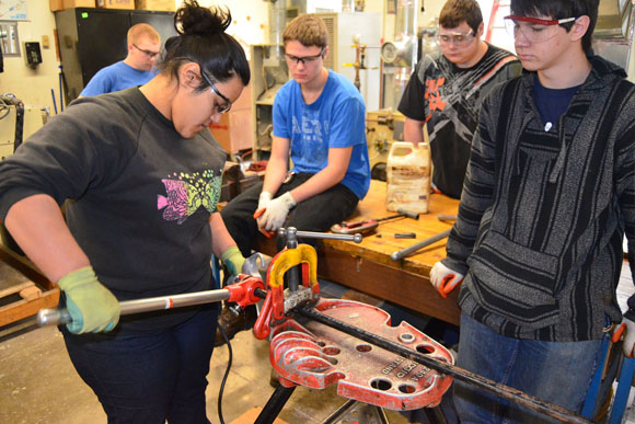 Students working on bending metal in a classtoom