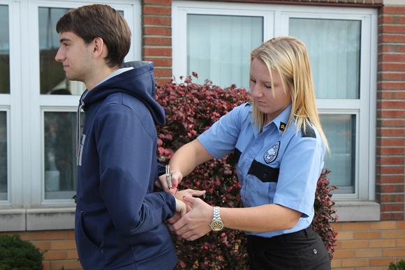 Criminal Justice student practices with handcuffs on a fellow student