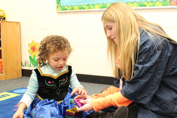Student shares a manipulative with a child