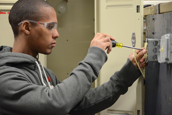 Electrical Construction student installs an outlet