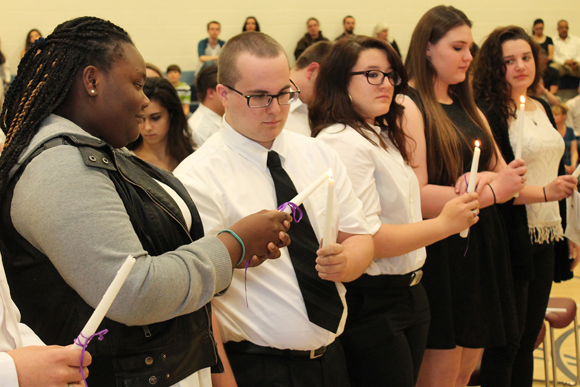 Students light each other's candles at National Technical Honor society candling lighting ceremony