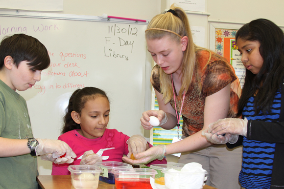 Students mixes up a concoction while three children look on