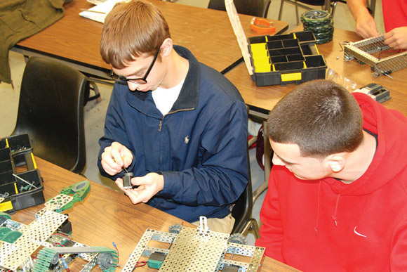 Two students work with small robotics parts