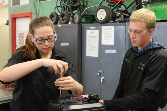Two students work on a small engine part