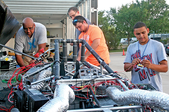 Two students and their instructor work on the solar car