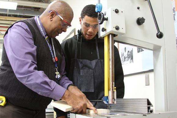 Transitional Occupations Program instructor works at lathe with student