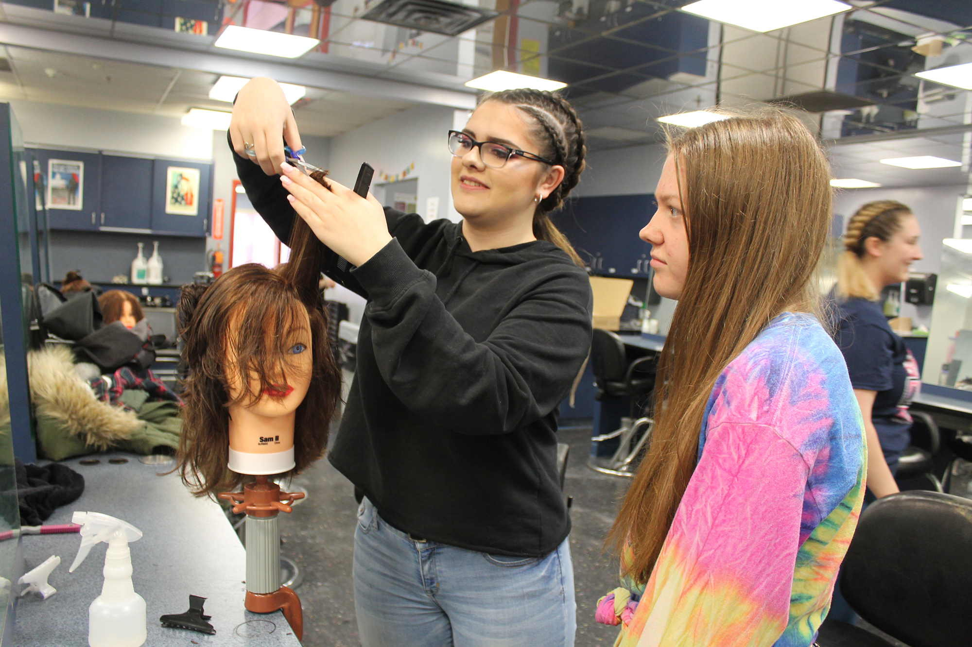 A Highland High School student observes a Cosmetology student demonstrate hair-cutting techniques.