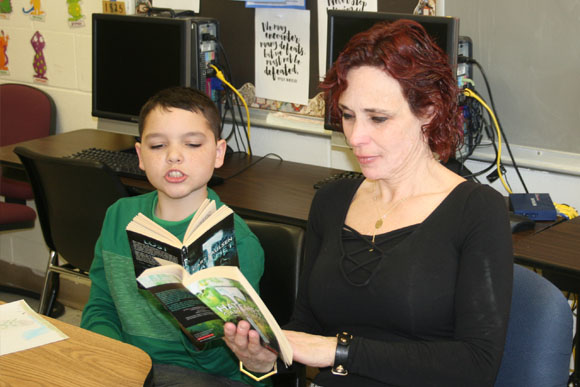 A young boy and his teacher reading together