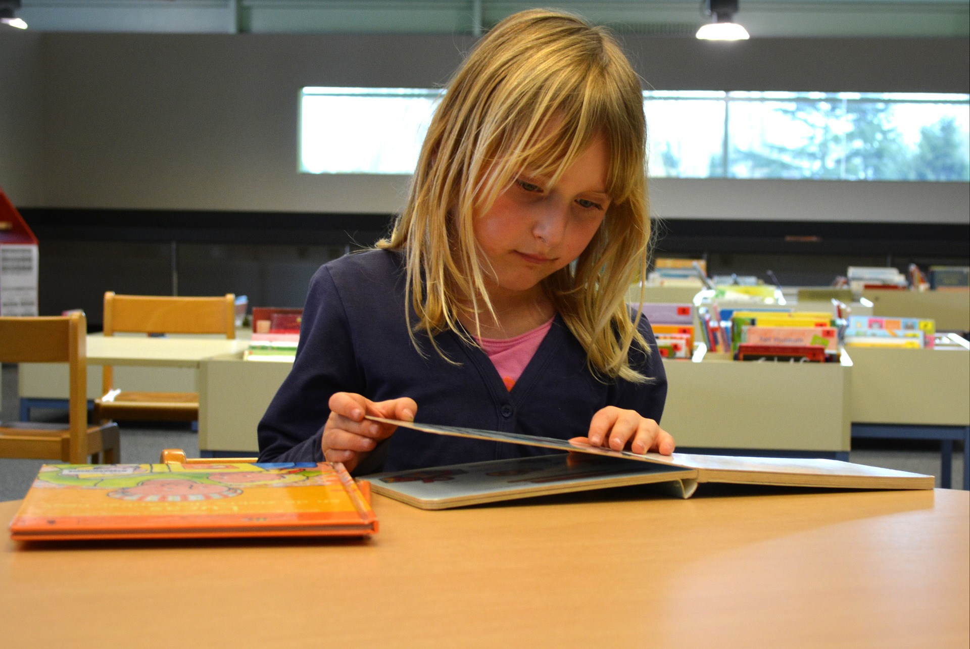 Blonde lower school student reading a book in the library.