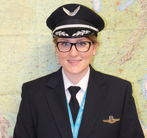 Katja Jourdan in her captain uniform in front of map.
